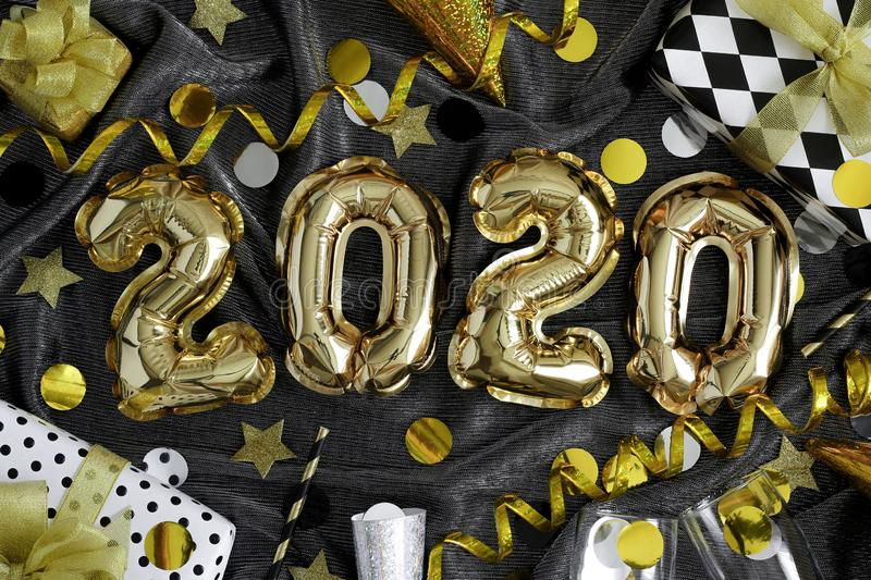 2020 - Happy New Year!. Happy New Year! 2020 golden balloons numbers, shiny streamers, confetti, wrapped  gift boxes and glasses of champagne on dark fabric royalty free stock photo