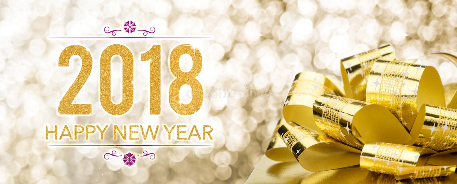 Happy new year 2018 with golden gift box with big bow at sparkling bokeh blur background,Holiday greeting card banner royalty free stock photo