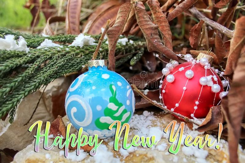 Happy New Year greeting card. Christmas balls. On natural stone, snow and trees stock images