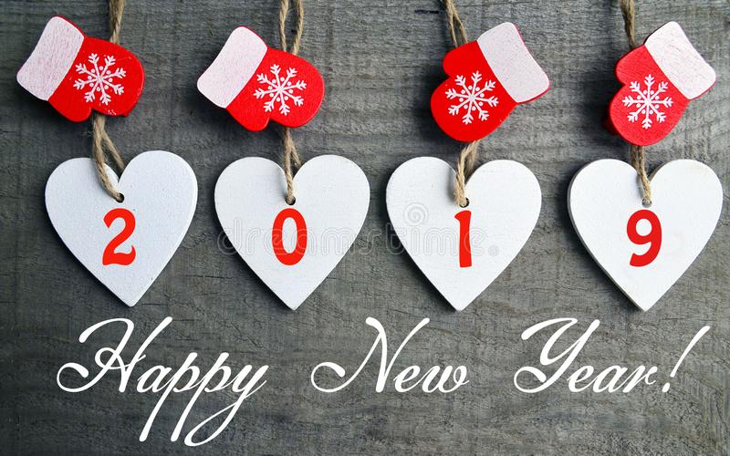 Happy New Year greeting card.Decorative white wooden Christmas hearts and red mittens with 2019 numbers on old wooden background. Happy New Year 2019 greeting royalty free stock images