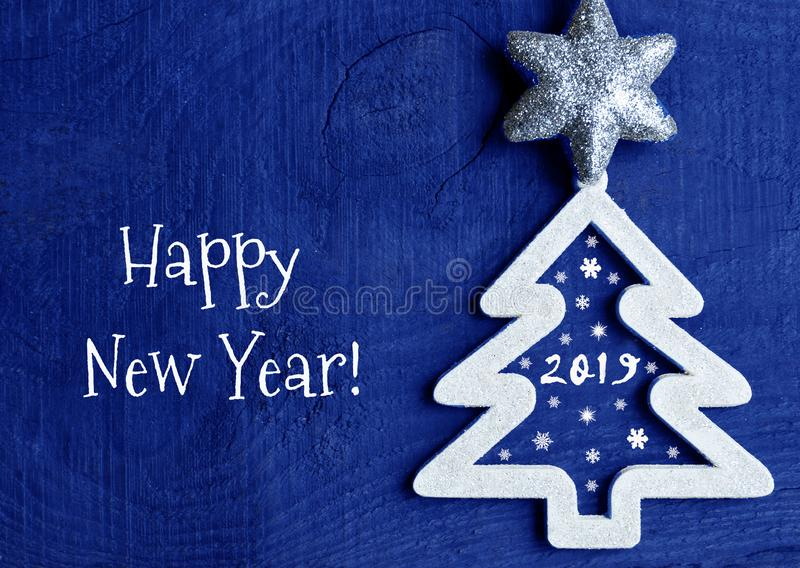 Happy New Year greeting card.White christmas tree with 2019 number on a dark blue wooden background. royalty free stock image