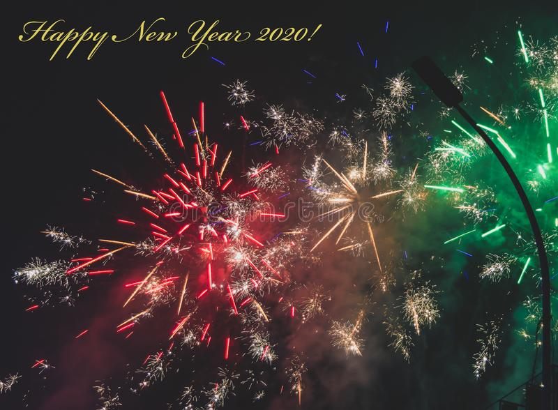 Happy New Year 2020 greeting card with yellow text and colorful firework on background royalty free stock photography