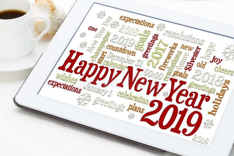 Happy New Year 2019 word cloud. Happy New Year 2019 greetings card - word cloud on a digital tablet with a cup of coffee stock photo