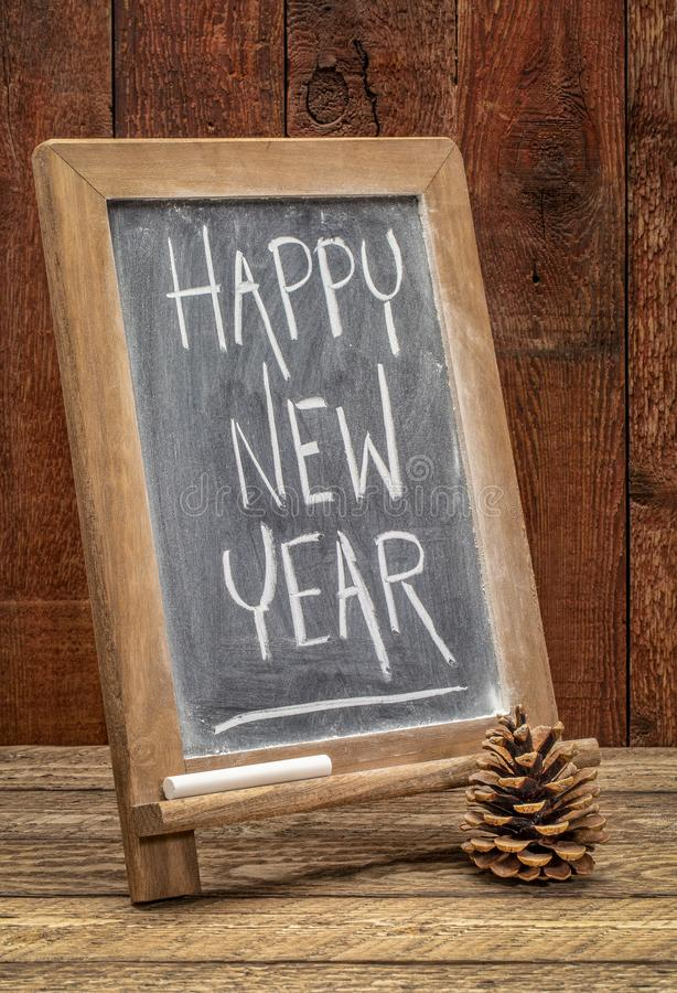 Happy new year blackboard sign. Happy new year greetings - white chalk text on a blackboard against barn wood royalty free stock photos