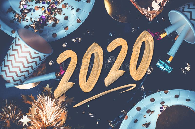 2020 happy new year hand brush storke font on marble table with party cup,party blower,tinsel,confetti.Fun Celebrate holiday party. Time table top view.blue royalty free stock photos