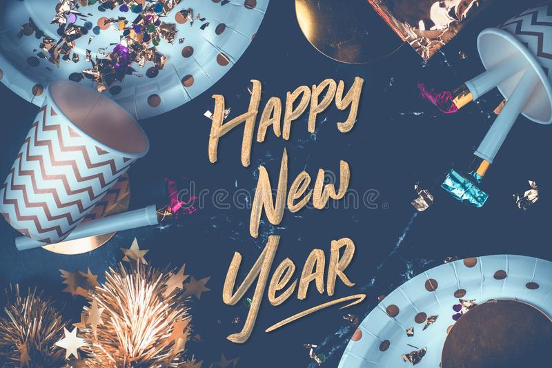 Happy new year hand brush stroke font on marble table with party. Cup,party blower,tinsel,confetti.Fun Celebrate holiday party time table top view.blue modern stock image