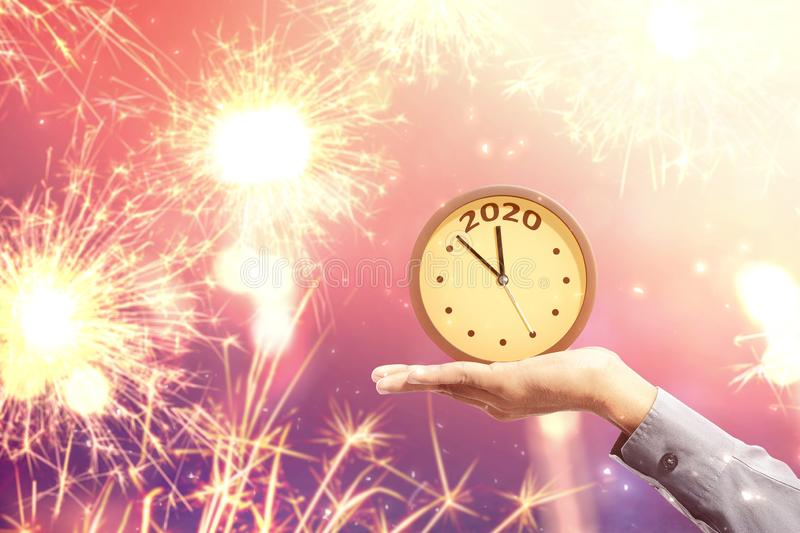 Happy New Year 2020. Hand holding a clock with fireworks background. Happy New Year 2020 stock photos