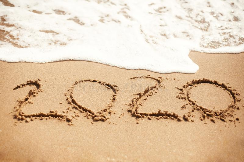 Happy New Year 2020, handwritten on sandy beach. 2020 numbers inscription on golden sand and waves foam at sea beach. Tropical. Celebration stock photos