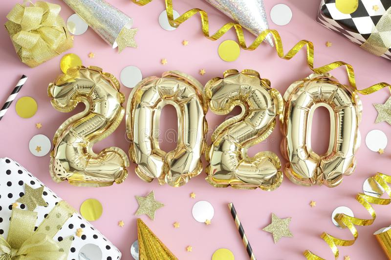 2020 - Happy New Year!. Happy New Year! 2020 golden balloons numbers, shiny streamers, confetti, wrapped  gift boxes and glasses of champagne on dark fabric royalty free stock images