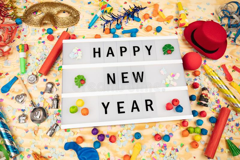 Happy New Year. Greetings on a lightbox with party dekoration stock photo
