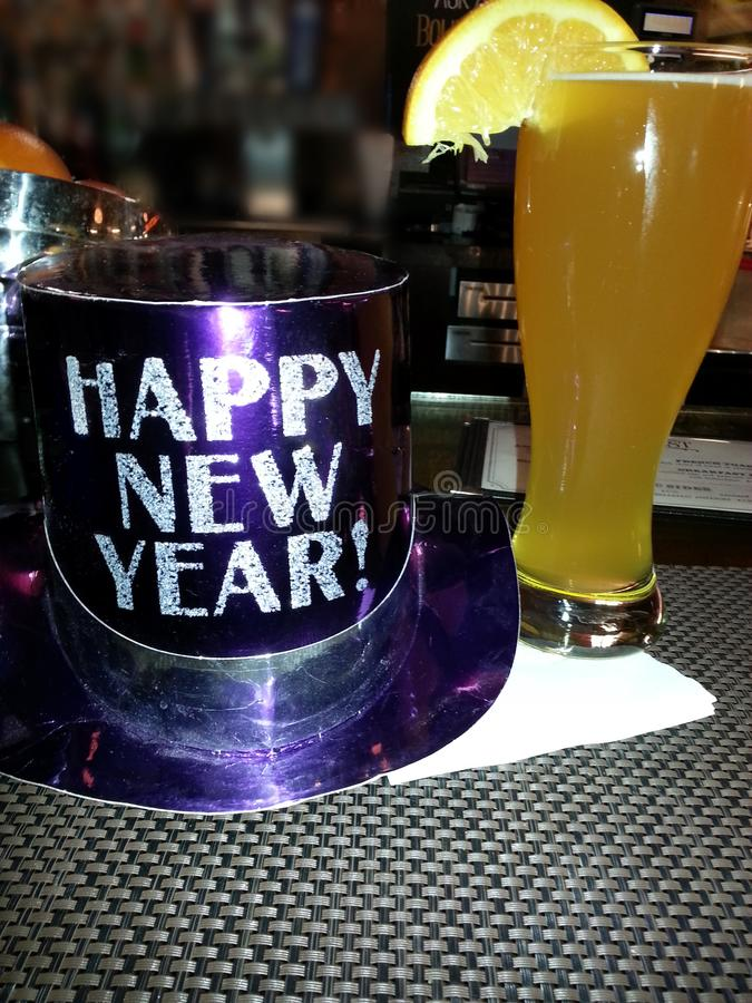 Happy New Year Hat with Beer. Happy new year`s Holiday celebration at the bar with drink and purple party hat having fun royalty free stock photography