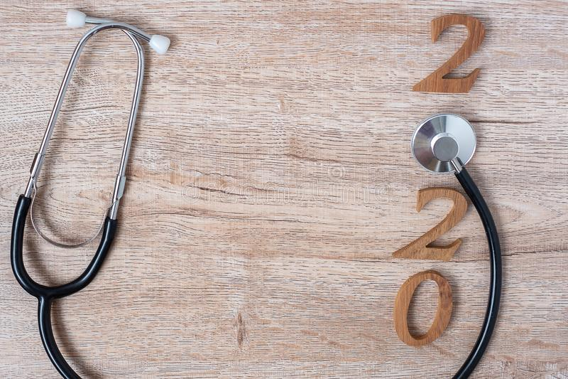 2020 Happy New Year for healthcare, Wellness and medical concept. Stethoscope with red heart and wooden number on table background.  royalty free stock images