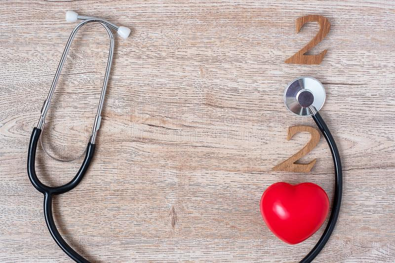 2020 Happy New Year for healthcare, Wellness and medical concept. Stethoscope with red heart and wooden number on table background.  stock photo
