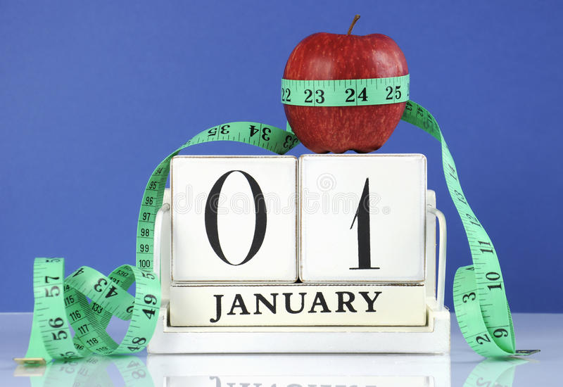 Happy New Year healthy slimming weight loss or good health resolution. With red apple and measuring tape on white wood vintage style calendar for January first royalty free stock image