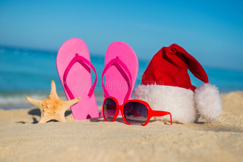 Happy New Year holidays and Merry Christmas at Sea. Sandals, sunglasses and santa hat on sandy beach royalty free stock images