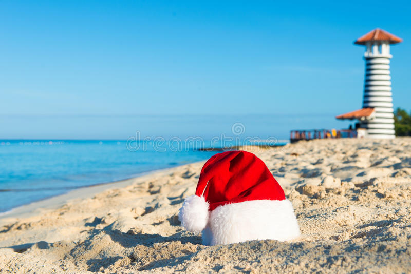 Happy New Year holidays at Sea. Santa hat on sandy beach - christmas holiday concept.  stock images