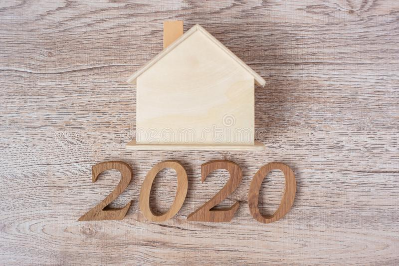 2020 Happy New Year with house model on wood table background with copy space. Financial, money, refinance, Real estate and new. Hone concept stock photos