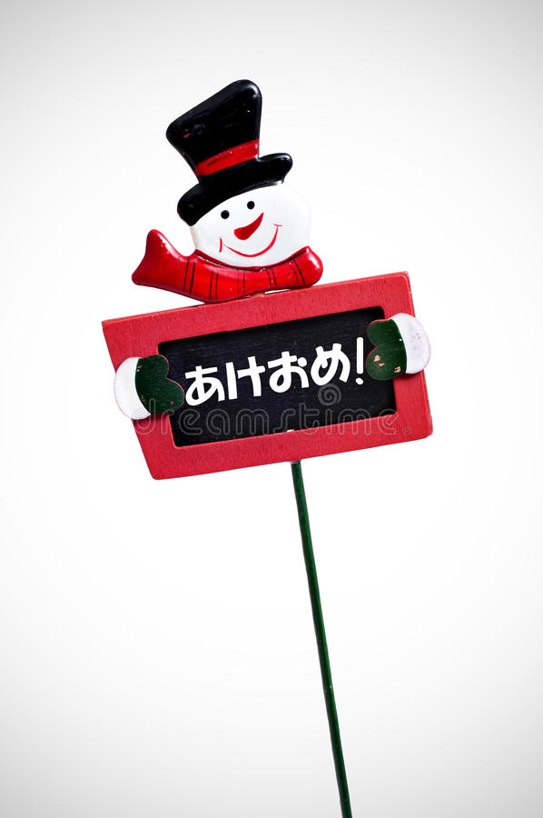 Happy new year in japanese. Happy new year written in japanese in a blackboard label with a snowman royalty free stock photography