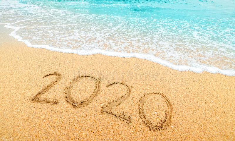 Happy New Year 2020, lettering on the beach with wave and  blue sea. Numbers 2020 year on the sea shore, New Years concept stock photos