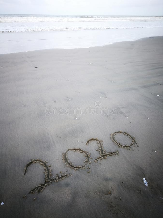 Happy new year 2020, lettering on the beach with wave and clear blue sea. Numbers 2020 year on the sea shore. stock photos