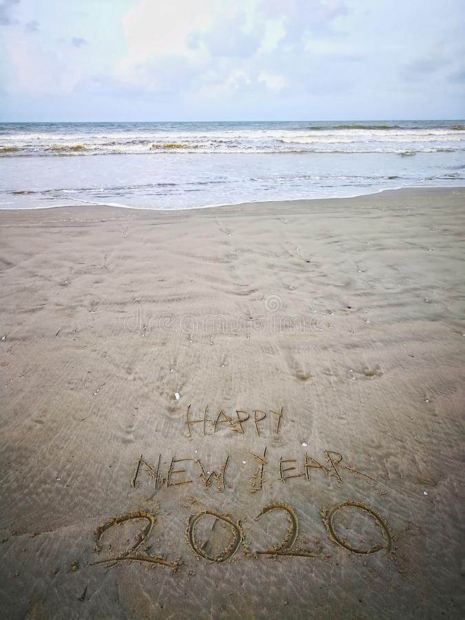 Happy new year 2020, lettering on the beach with wave and clear blue sea. Numbers 2020 year on the sea shore. stock photography