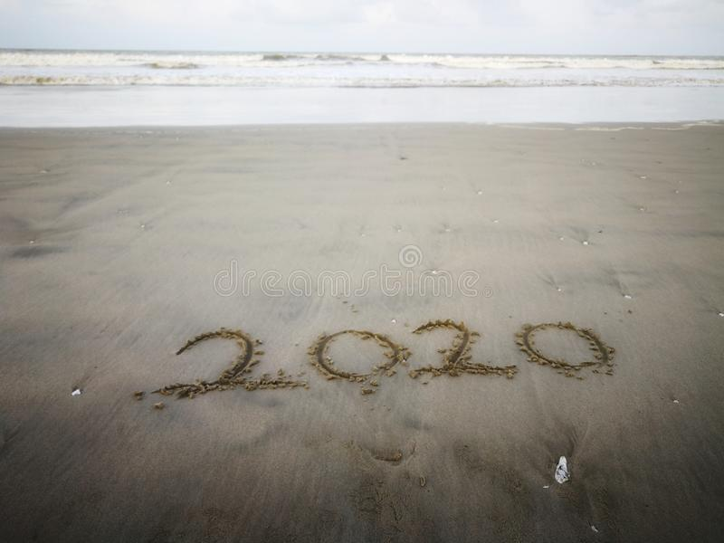 Happy new year 2020, lettering on the beach with wave and clear blue sea. Numbers 2020 year on the sea shore. royalty free stock photo