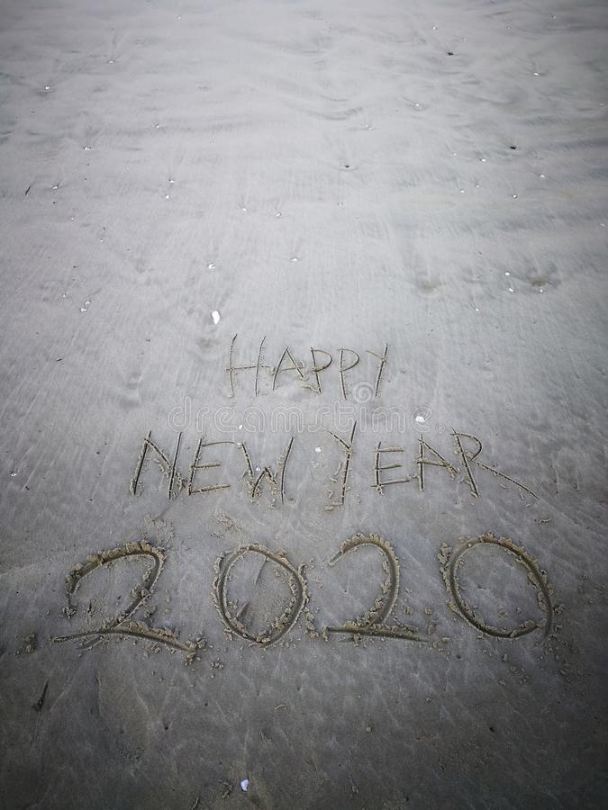 Happy new year 2020, lettering on the beach with wave and clear blue sea. Numbers 2020 year on the sea shore. stock images