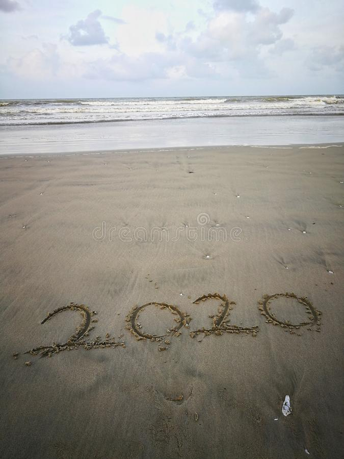 Happy new year 2020, lettering on the beach with wave and clear blue sea. Numbers 2020 year on the sea shore. royalty free stock image