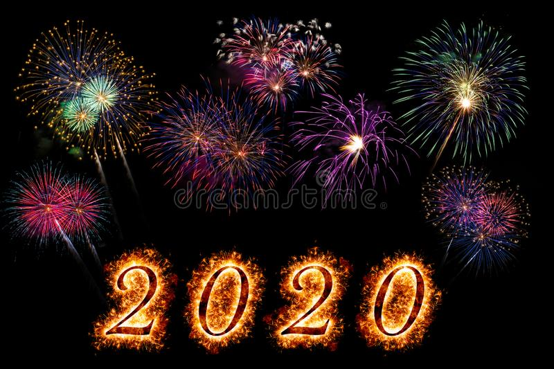 Happy New Year 2020 letters with sparkle and fireworks on black background royalty free stock images