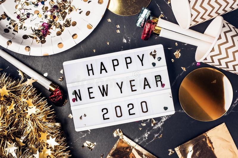 Happy new year 2020 on light box with party cup,party blower,tinsel,confetti.Fun Celebrate holiday party time table top view stock images