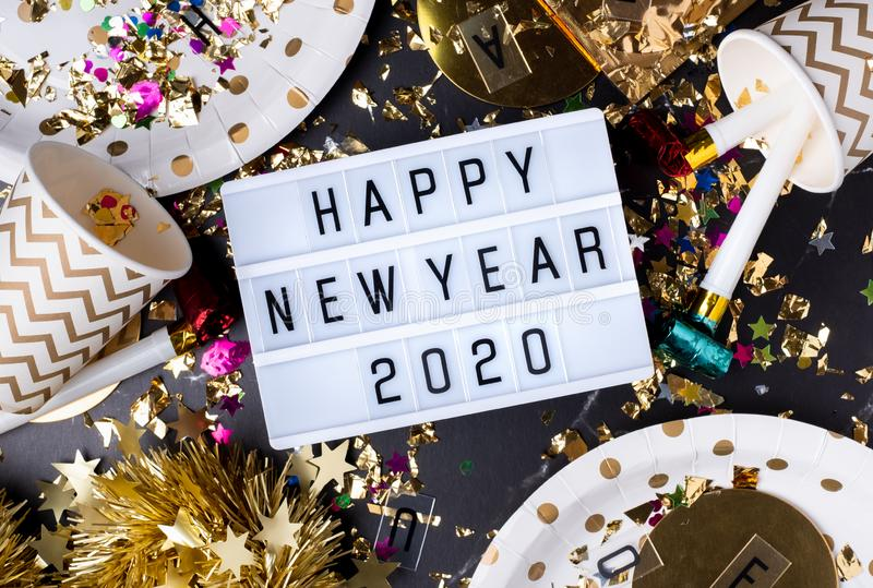 Happy new year 2020 on light box with party cup,party blower,tinsel,confetti.Fun Celebrate holiday party time table top view.  royalty free stock photo