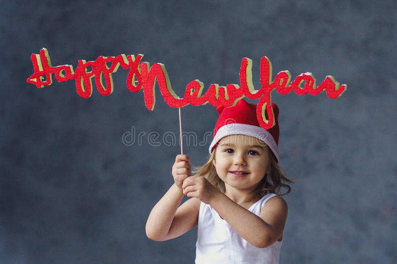 Happy New Year. Little Santa girl is holding a sign happy new year royalty free stock photography