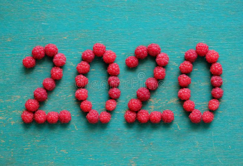 Happy new year 2020 made of berries on a blue wooden background royalty free stock photo