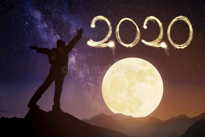 Happy new year 2020.man on top of the mountain looking the moon. New year 2020.man on top of the mountain looking the moon royalty free stock images