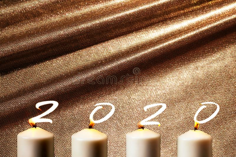 Happy New Year 2020. Marry Christmas and happy New Year. 2020 is written with candle flames on golden bronze background. Concept of greeting card. Top view royalty free stock photo