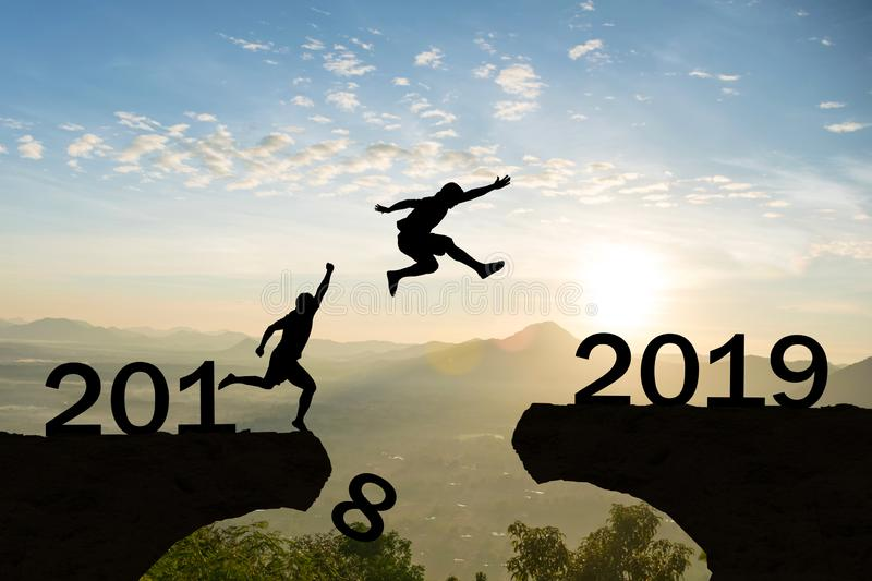 Happy New Year 2019 Men jump over silhouette mountains stock images