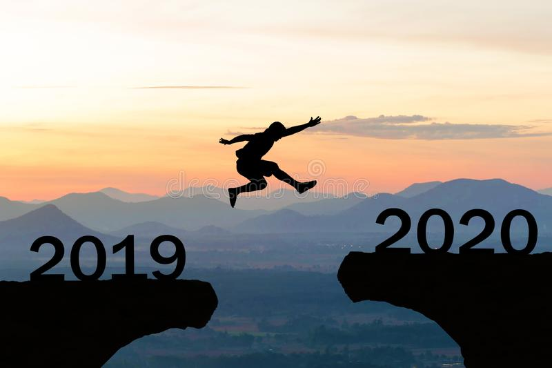 Happy New Year 2020 Men jump over silhouette mountains stock photo