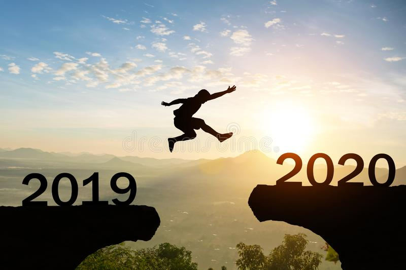 Happy New Year 2020 Men jump over silhouette mountains royalty free stock photos
