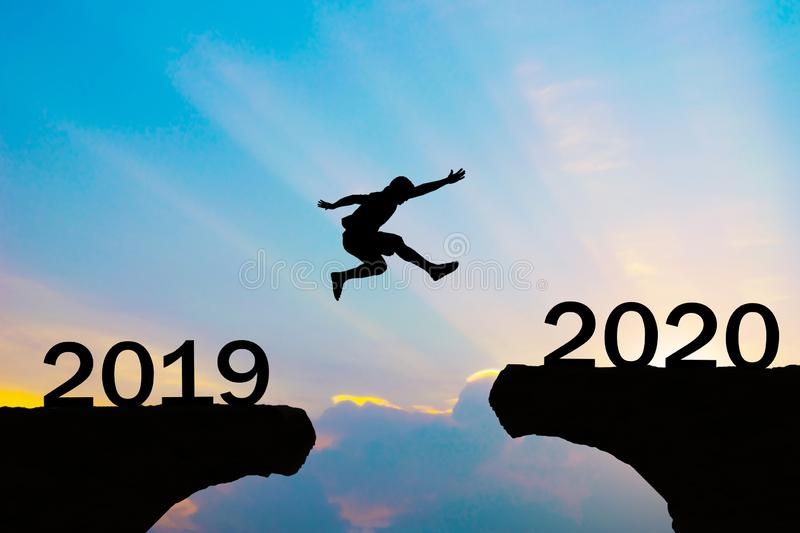 Happy New Year 2020 Men jump over silhouette mountains royalty free stock images