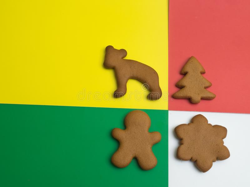 Happy New Year and Merry Christmas gingerbread on a red yellow green white background. Christmas baking. Making gingerbread christ stock image