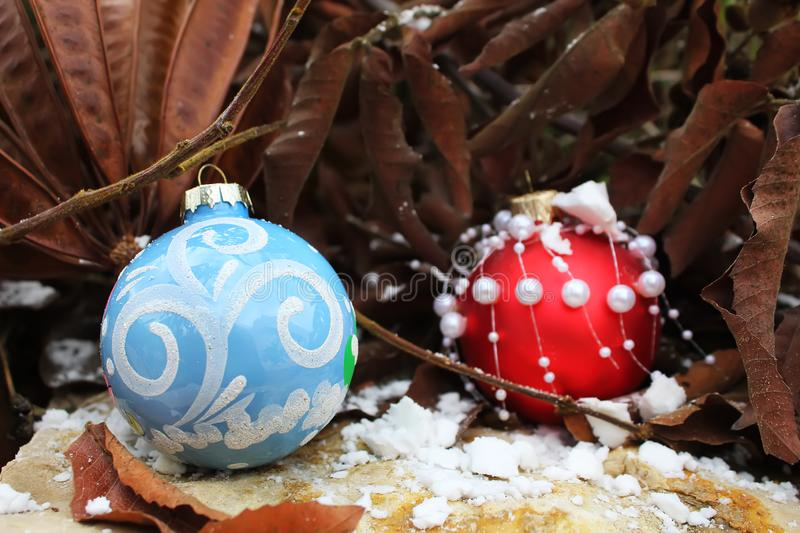Happy New Year or Merry Christmas greeting card. Two Christmas balls. On natural stone, snow and trees stock images
