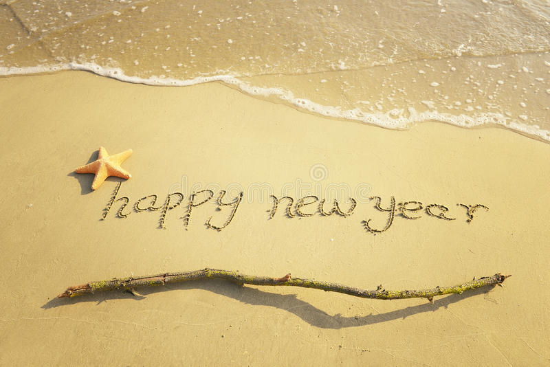 Happy new year message on the sand. Beach stock photos