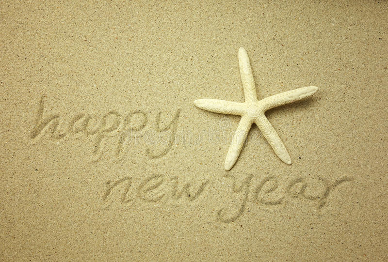Happy new year message on the sand. Beach stock image