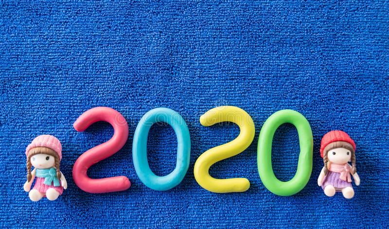 Happy New Year 2020 , molding color clay with cute girls dolls on blue towel. Happy New Year 2020 , molding color clay with cute girls dolls on blue. 2020, aqua stock photography