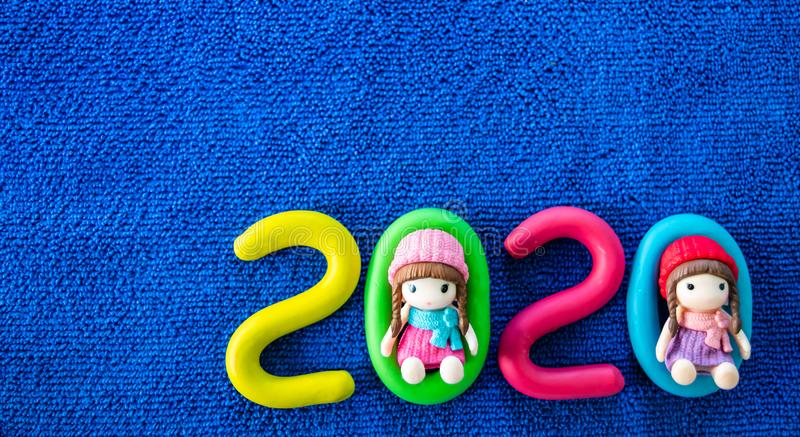 Happy New Year 2020 , molding of color clay with little girls toys on blue background. royalty free stock image