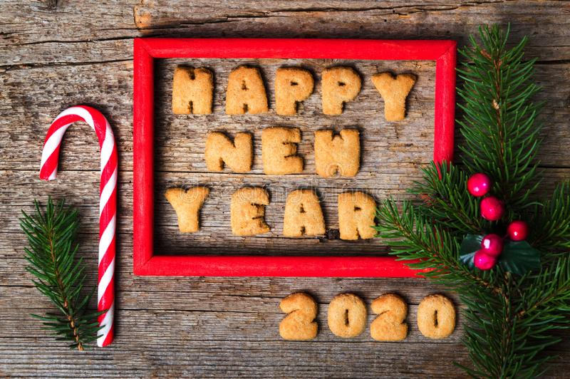Happy new year note in a wooden frame. Happy new year note in a red wooden frame, 2020, card, cookie, lollipop, christmas, mistletoe, pine, tree, branch, framed royalty free stock image