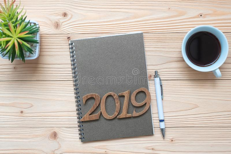 2019 Happy New Year with notebook, black coffee cup, pen and glasses on wooden table, Top view and copy space. New Start, Goals, R royalty free stock photo