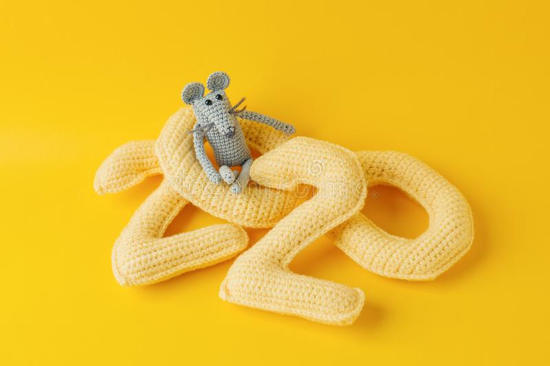 Happy New Year 2020. Number 2020 knitted from yarn and gray toy mouse symbol of year on bright yellow background, cheese color. Fl. At lay, top view, copy space stock photography