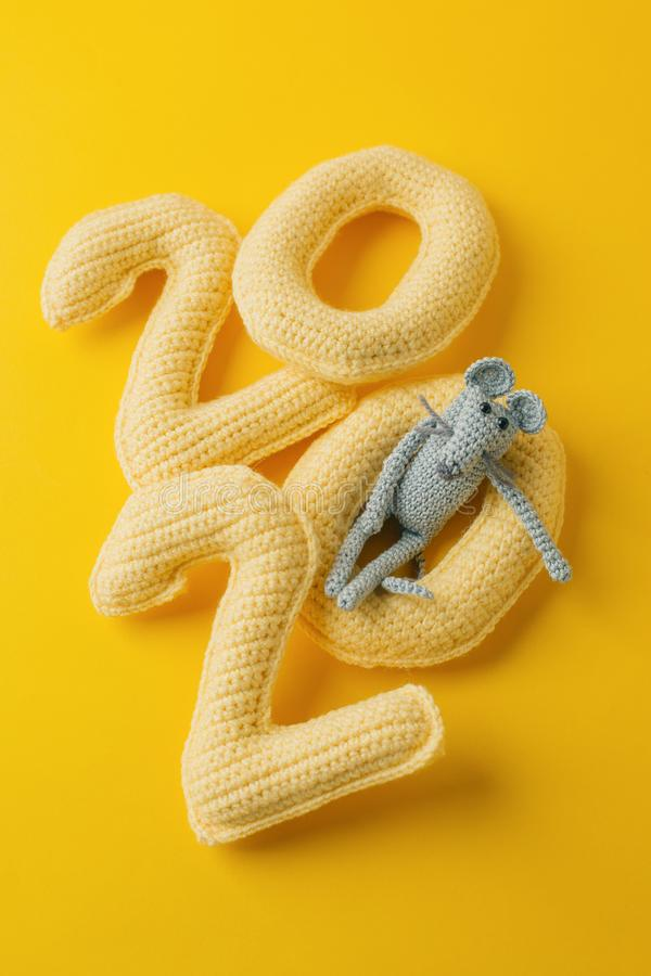 Happy New Year 2020. Number 2020 knitted from yarn and gray toy mouse symbol of year on bright yellow background, cheese color. Fl. At lay, top view, copy space stock photo