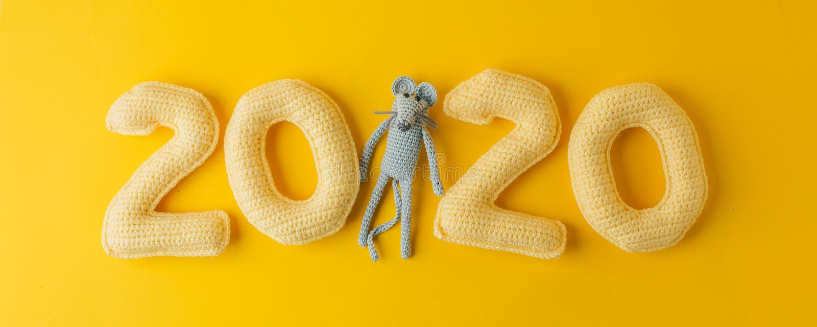 Happy New Year 2020. Number 2020 knitted from yarn and gray toy mouse symbol of year on bright yellow background, cheese color. Happy New Year 2020. Number 2020 stock photo